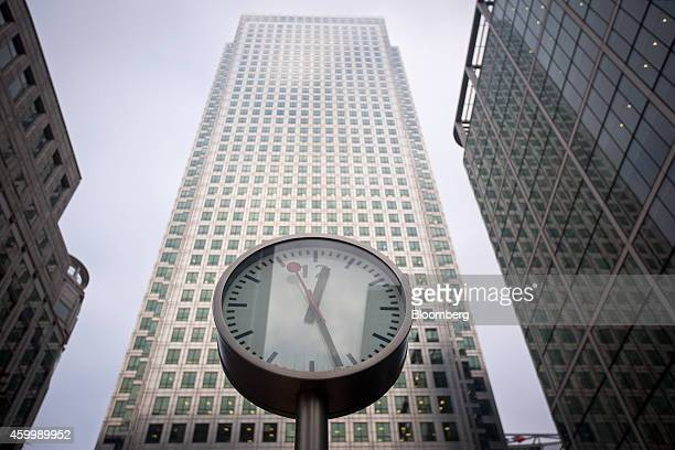 Clock displays the time in front of the One Canada Square office block, center, in the Canary Wharf business, financial and shopping district of...