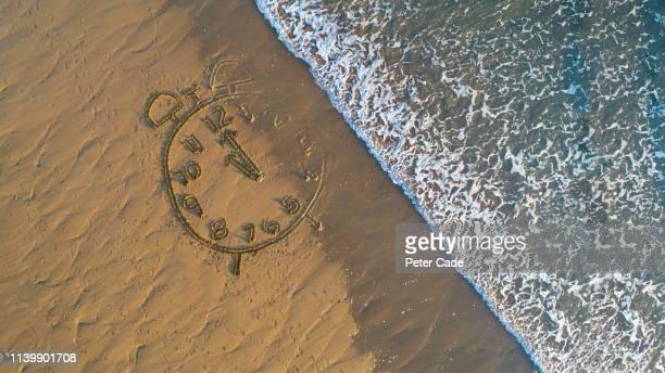 clock drawn in sand at water's edge - marea fotografías e imágenes de stock