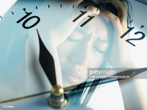 Clock face with reflection of woman holding head