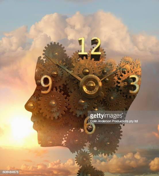 Clock forming silhouette of heads in clouds