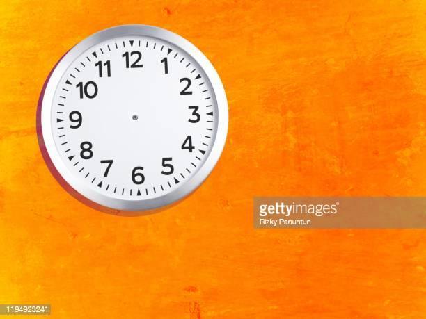clock hanging on a orange wall - ver a hora imagens e fotografias de stock