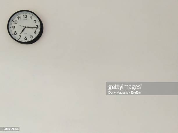 clock hanging on wall - wall clock stock photos and pictures