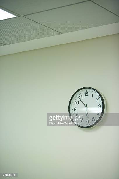clock hanging on wall under fluorescent light - wall clock stock photos and pictures