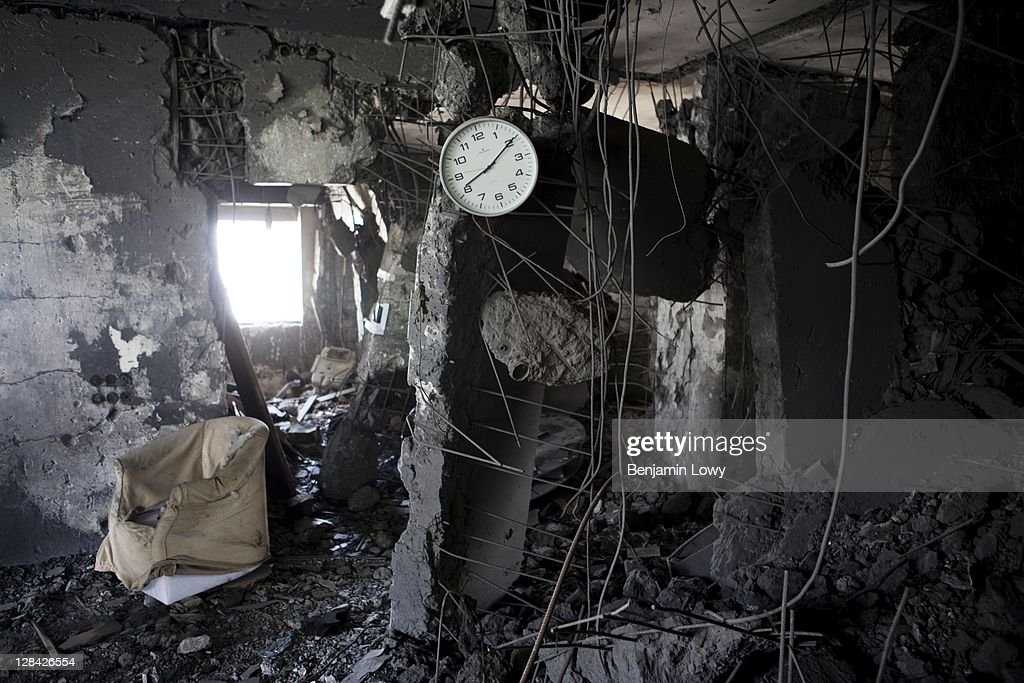 A clock hangs from the shattered remains of a wall in the NATO bombed home of former Libyan dictator Moammar Gaddafi's son Motasem, on September 2 2011 in Tripoli, Libya.