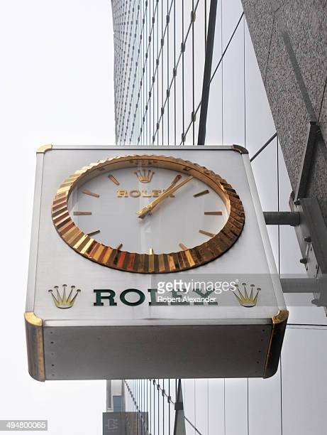 A clock hangs over the sidewalk entrance to a Rolex store in the Ginza district of Tokyo Japan