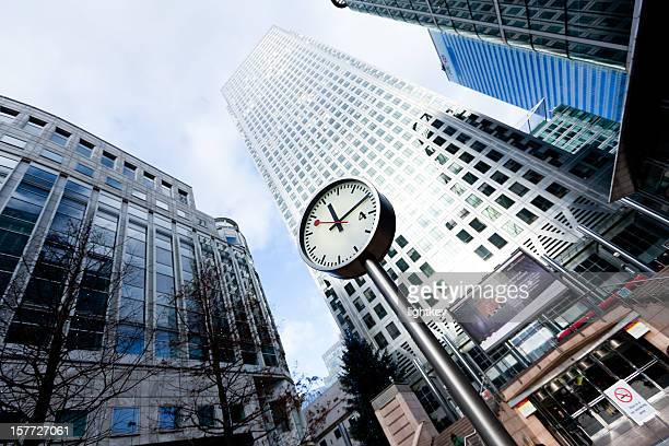 clock in financial district of london - canary wharf stock photos and pictures