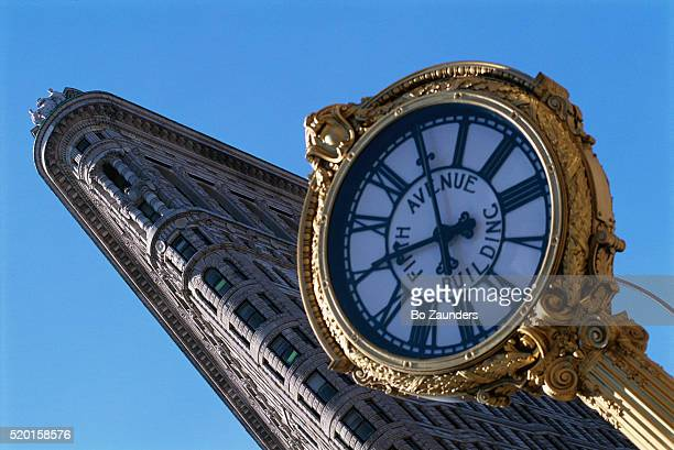 clock in front of flatiron building in new york - bo zaunders stock pictures, royalty-free photos & images