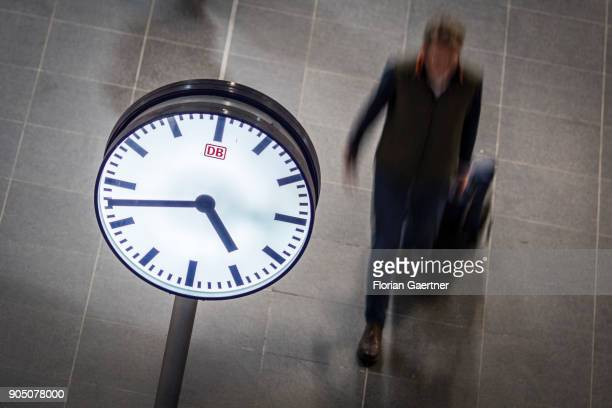 A clock is pictured in front of a walking traveller on January 11 2018 in Berlin Germany