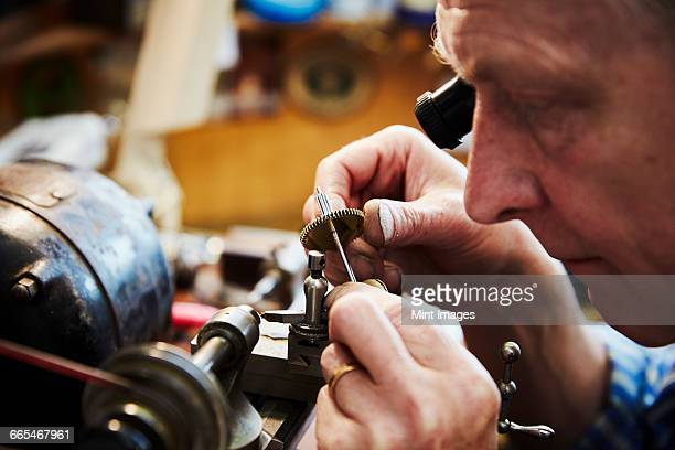 A clock maker busy in his workshop.