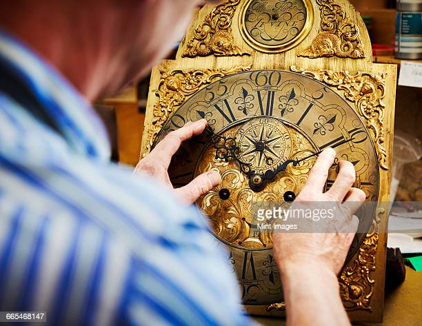 A clock maker displaying his work.