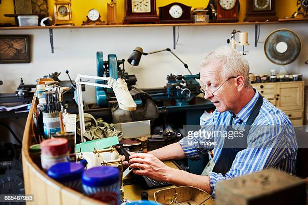 Clock maker in his workshop using a laptop.