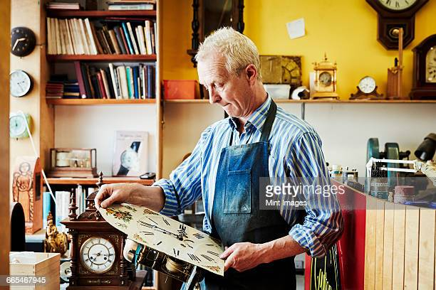 A clock maker viewing his work in the workshop.