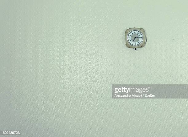 clock mounted on wall - alessandro miccoli stock photos and pictures