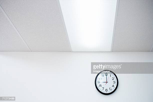 clock on an office wall - fluorescent light stock pictures, royalty-free photos & images