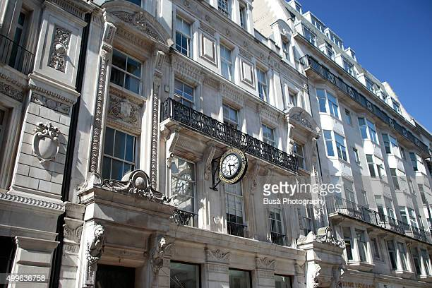 Clock on the facade of a building at 58 Jermyn St, London, UK