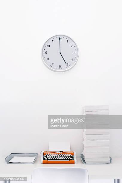Clock on wall above typewriter and 'in and 'out' trays