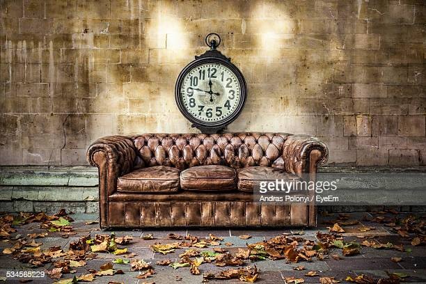 Clock On Wall In Front Of Sofa On Sidewalk During Autumn