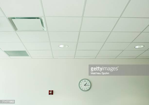 clock on wall in office space - ceiling stock pictures, royalty-free photos & images