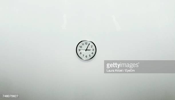 clock on white wall at home - wall clock stock photos and pictures