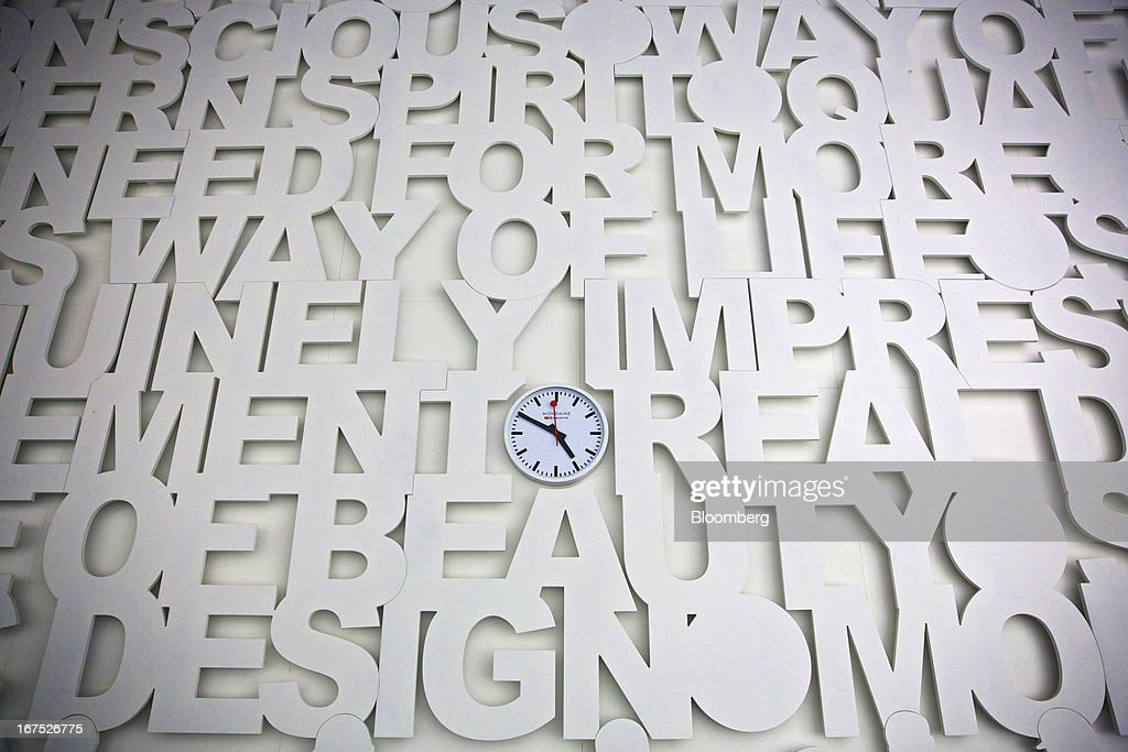 A clock sits in the center of a wall display at the Mondaine Watch Ltd. booth during the Baselworld watch fair in Basel, Switzerland, on Thursday, April 25, 2013. The annual fair attracts 2,000 companies from the watch, jewelry and gem industries to show their new wares to more than 100,000 visitors. Photographer: Gianluca Colla/Bloomberg via Getty Images