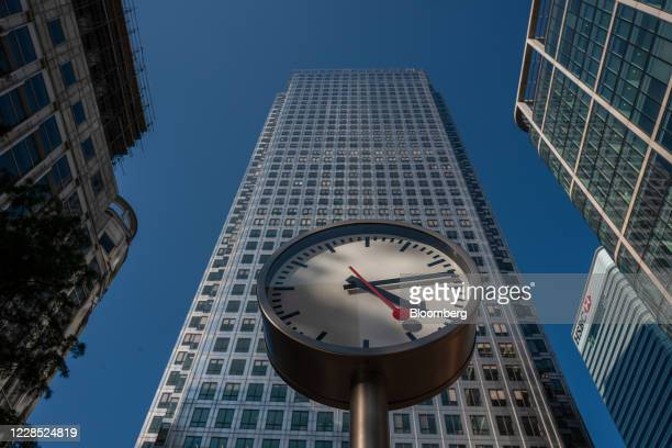 Clock stands in front of the One Canada Water skyscraper office building in the Canary Wharf business, financial and shopping district of London,...