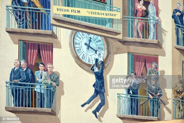 Clock Stunt (centre) from 'Safety First' (1923) by Harold Lloyd. Mural Wall Paintings Celebrating Movie History, Bus Station, Cannes