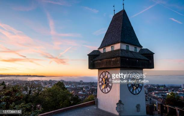 clock tower amidst buildings against sky during sunset - austria stock pictures, royalty-free photos & images