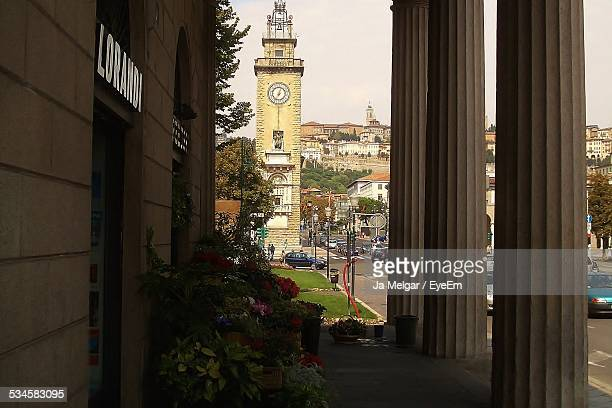 clock tower and architectural columns by city street - bergamo alta foto e immagini stock