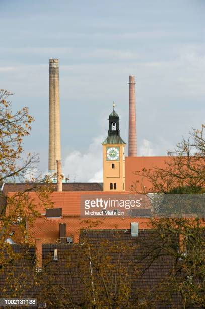 Clock tower and two chimneys in the historic town of Augsburg, Swabia, Bavaria, Germany