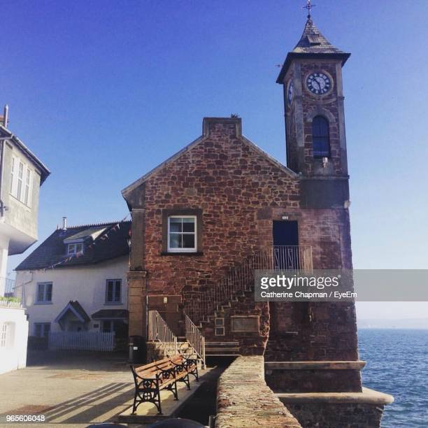 clock tower by sea against clear sky, cawsand - clock tower stock pictures, royalty-free photos & images