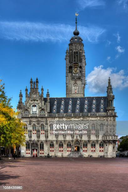 clock tower in city against sky - middelburg netherlands stock pictures, royalty-free photos & images