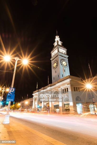 Clock Tower of San Francisco Ferry Building at Night with Street Light and Long Exposure of Flowing Traffic
