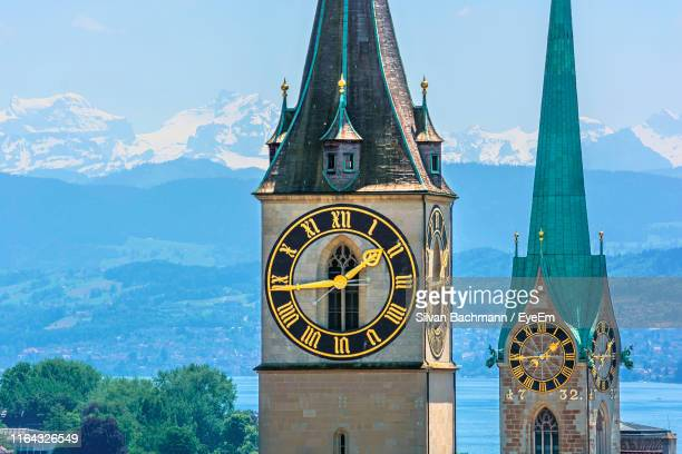 clock towers in city against sky - zurich stock pictures, royalty-free photos & images
