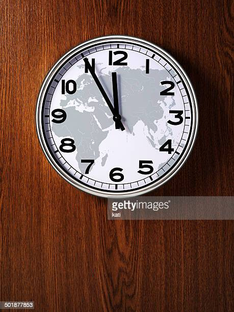 Clock with a map of Europe, Africa, Asia, Australia, five minutes to midnight