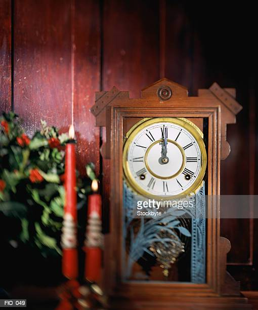 Clock with Christmas candles and wreath beside it