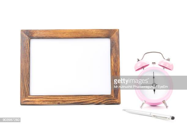 Clock With Picture Frame And Pen Over White Background