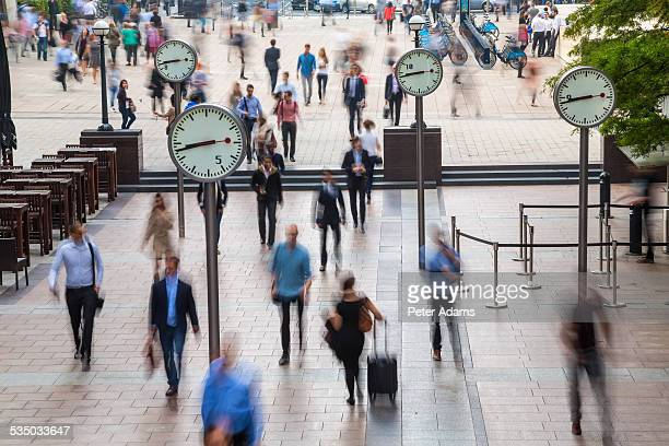 clocks and commuters, canary wharf, london - canary wharf stock pictures, royalty-free photos & images