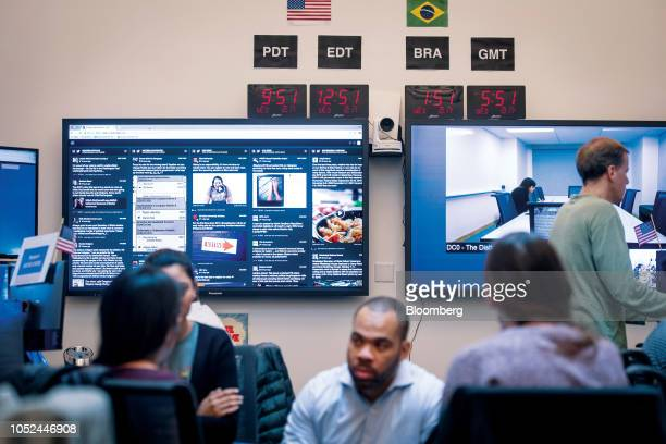 Clocks are displayed above monitors as employees work inside the War Room ahead of Brazil's runoff election at Facebook Inc headquarters in Menlo...