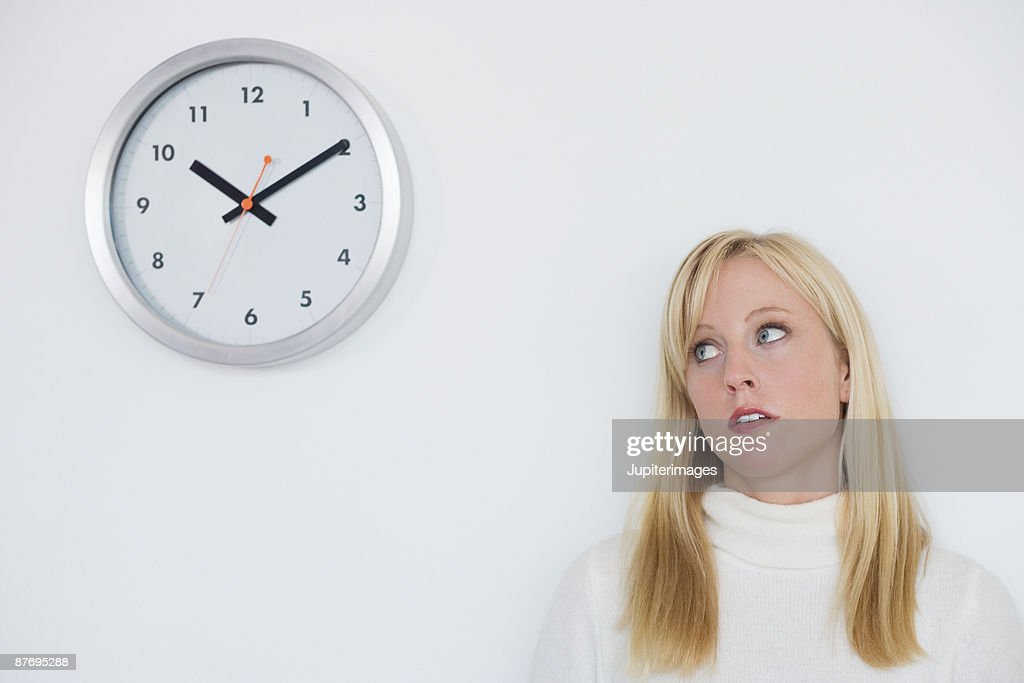 Clock-watching woman in office : Stock Photo