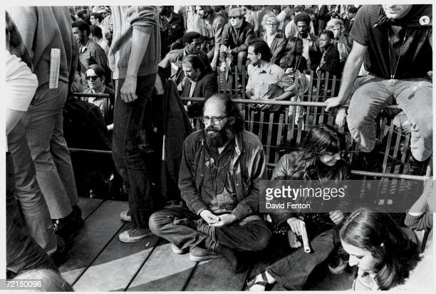 Clockwise from left American Beat poet Allen Ginsberg sits with his hands clasped together in a meditative crosslegged stance next to social worker...