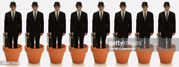 Cloned Businessmen Growing from Flower Pots
