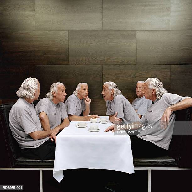 clones of mature man at table - cloning stock pictures, royalty-free photos & images