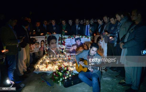 A close friend of slain Afghan AFP reporter Sardar Ahmad plays the guitar during a candle light vigil in his honour on a hill overlooking Kabul on...
