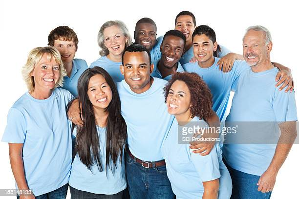Close group of people together, all in blue shirts