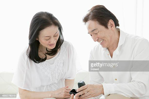a close middle-aged couple - engagement ring box stock photos and pictures