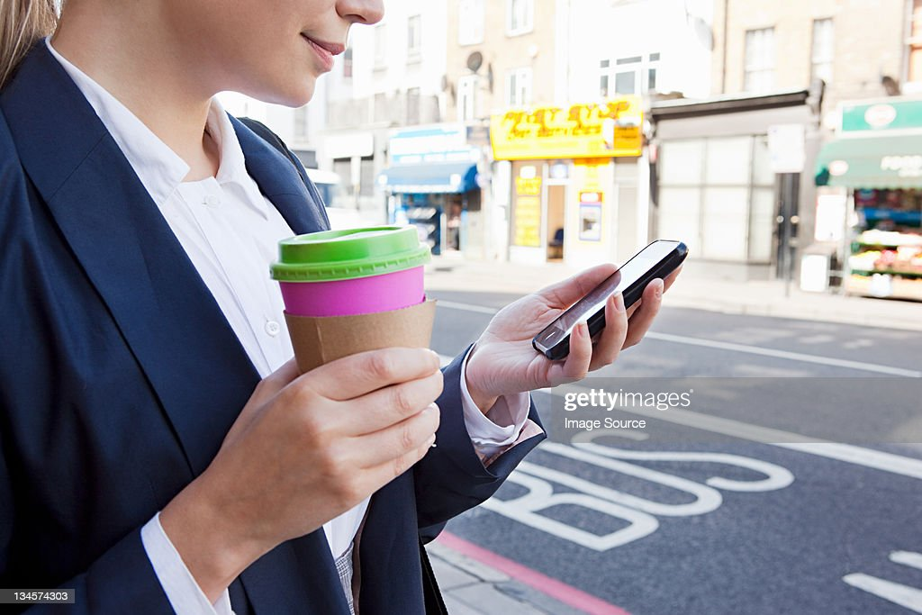 Close of businesswoman on street with coffee and smart phone : Stock Photo