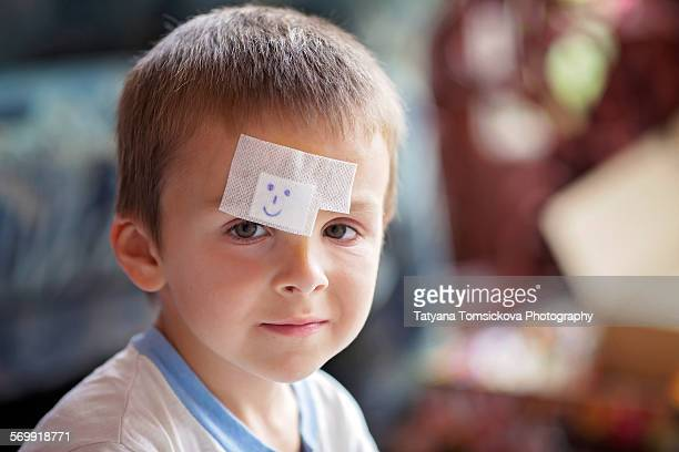 Close portrait of a boy with band aid on forehead