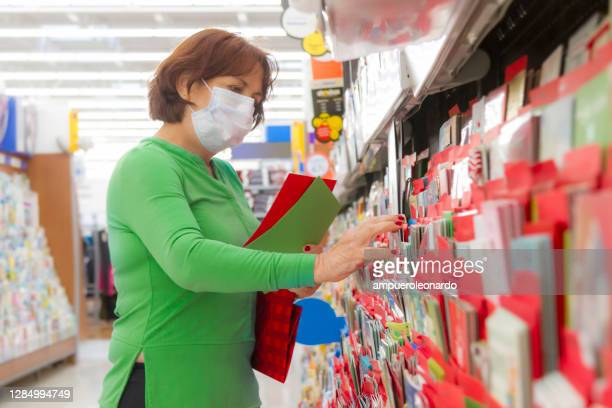 close portrait of latin mature woman choosing and shopping a christmas card in united states wearing a face mask during corona virus covid-19 pandemic illness breakdown - gift shop stock pictures, royalty-free photos & images
