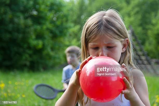 close portrait of young girl blowing up red balloon - sigrid gombert stockfoto's en -beelden