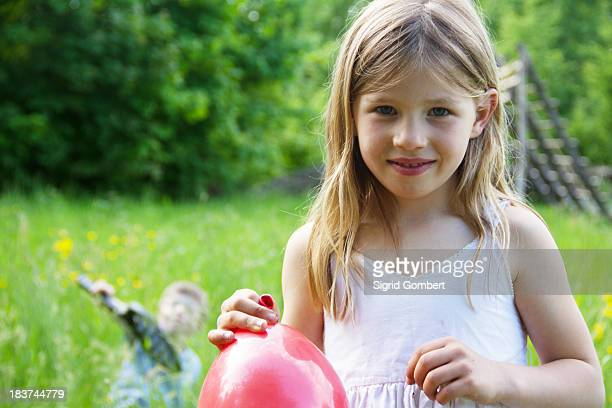 close portrait of young girl holding red balloon - sigrid gombert stock pictures, royalty-free photos & images
